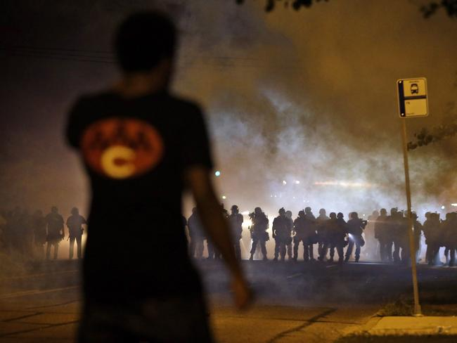 A man watches as police walk through a cloud of smoke during a clash with protesters on Wednesday night. AP Photo/Jeff Roberson