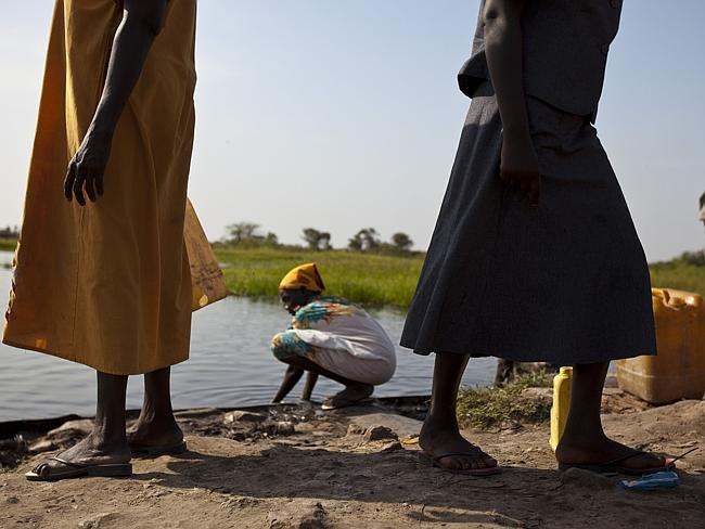 Running for their lives ... women collect water at the Nam river in Bentiu after fleeing clashes.