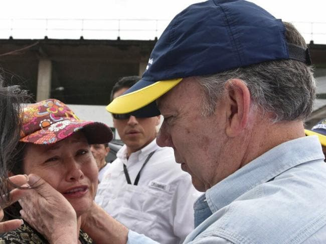 Colombian President Juan Manuel Santos comforting a resident while visiting the area affected by heavy rains, in Mocoa, Putumayo. Picture: AFP