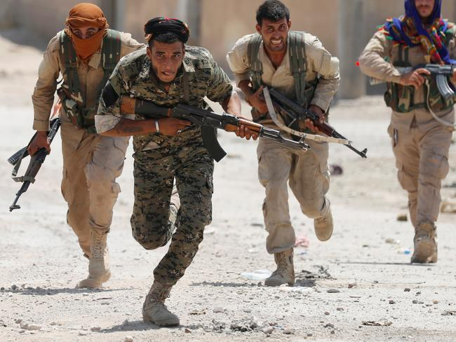 Kurdish fighters from the People's Protection Units (YPG) run across a street in Raqqa, Syria. Picture: Reuters