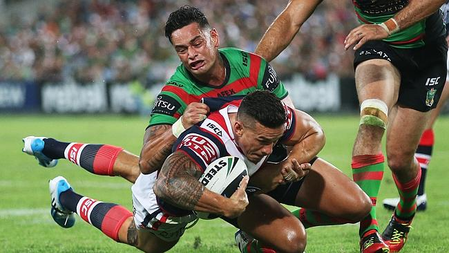 Rooster's Sonny Bill Williams on the attack ahead of South Sydney's John Sutton. pic. Phil Hillyard