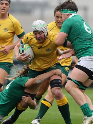 Chloe Butler of Australia is tackled by Nora Stapleton (L) and Ciara Griffin.