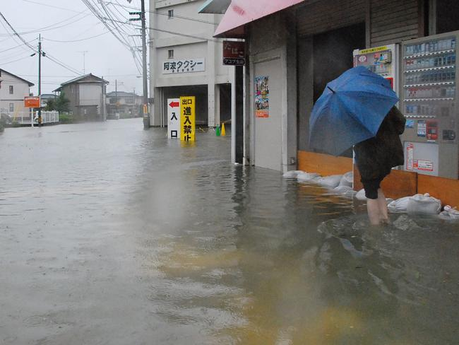 Drenched ... A local resident walks in a flooded street caused by Typhoon Halong's passing in Tokushima today. Source: AFP