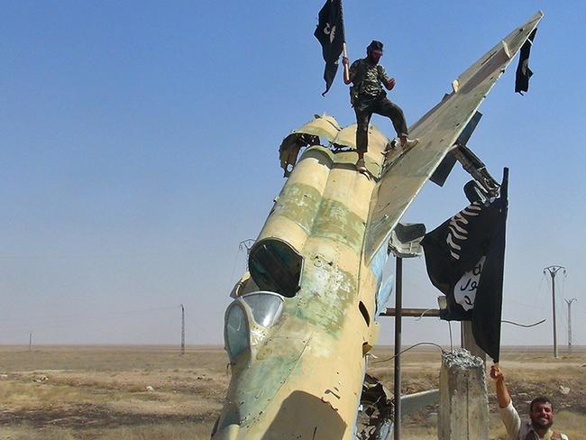 Fighters of the Islamic State waving the group's flag from a damaged display of a government fighter jet.