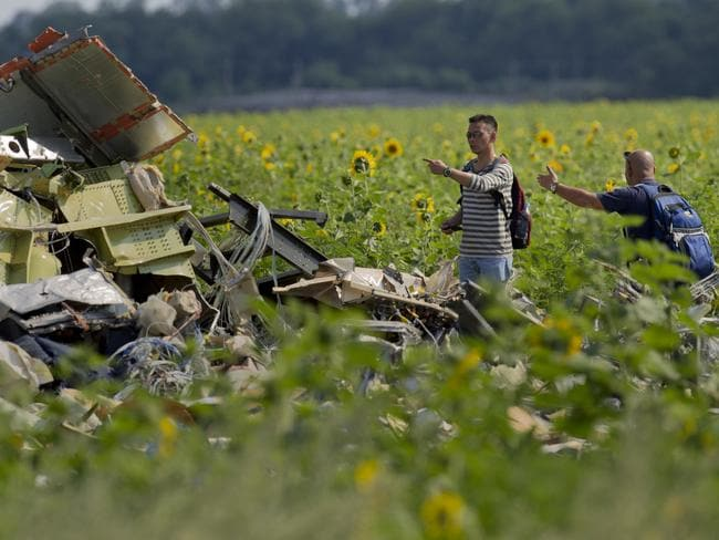 Safety an issue ... Malaysian air crash investigators inspect one of the crash sites. Picture: Vadim Ghirda