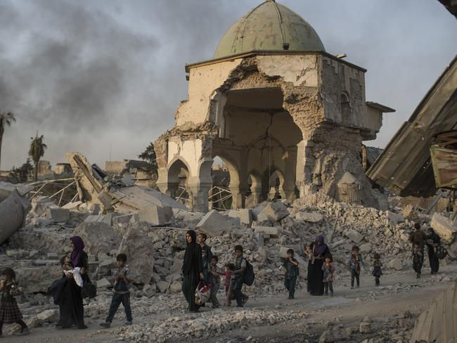Large parts of Mosul have been destroyed by IS which has ruined many ancient buildings and looted artefacts. Pictured, fleeing civilians walk past the heavily damaged al-Nuri mosque in Mosul's old city. Picture: AP Photo/Felipe Dana
