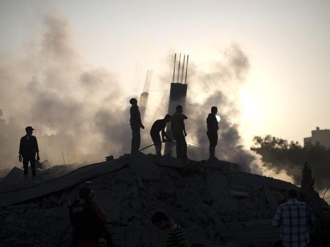 Aftermath ... Palestinian men inspect the site of an Israeli military strike in Gaza City.