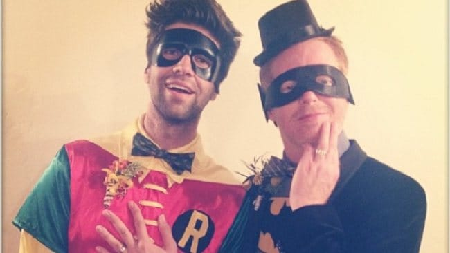Jesse Tyler Ferguson (right) and husband Justin Mikita flash their wedding rings as Batman and Robin