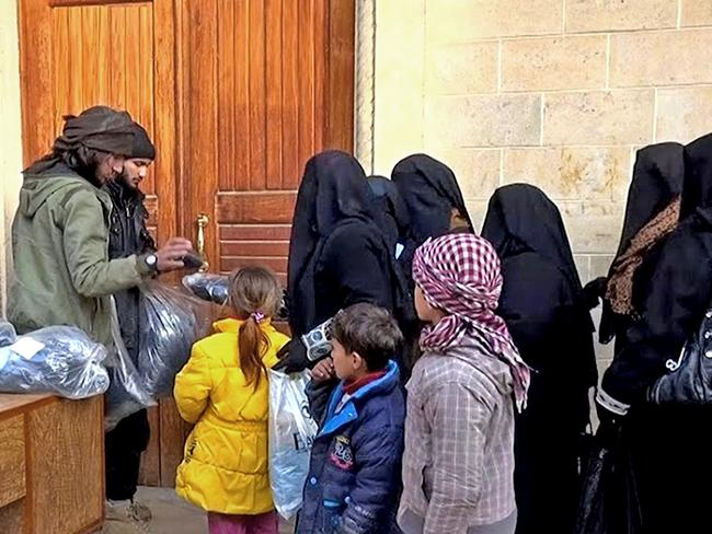 Members of the Islamic State group ... left, distribute niqabs, enveloping black robes and veils that leave only the eyes visible, to Iraqi women in Mosul, northern Iraq. Picture: AP via militant website