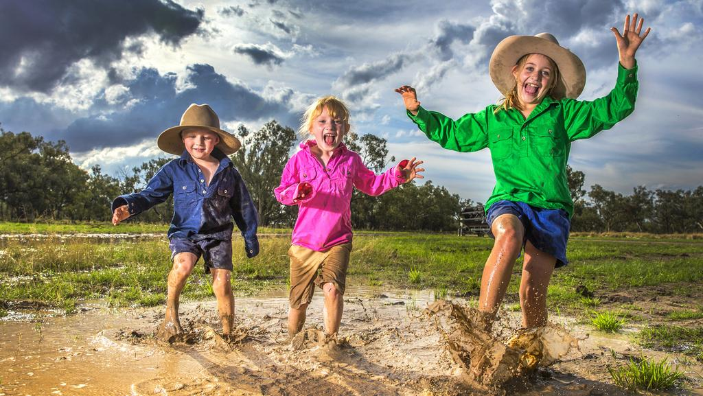The Willis kids — Cameron, 4, Kate, 6, and Claire, 9 — splash through the mud and puddles of their Bullamon Plains property near Thallon, about 400km west of Toowoomba. Picture: Nigel Hallett