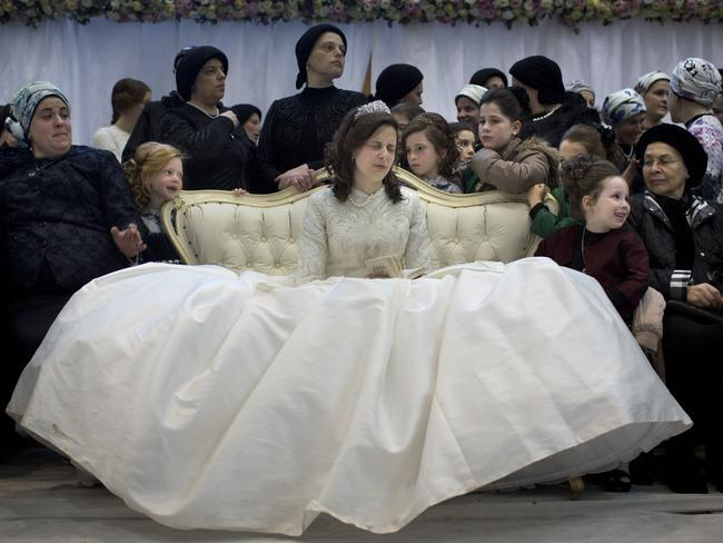 The bride sits with family members in the women's section. Picture: AP Photo/Oded Balilty