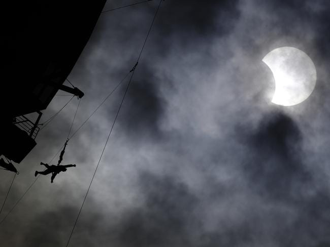 A person jumps off the top of the Stratosphere hotel and casino tower on the SkyJump ride during the solar eclipse, in Las Vegas. Picture: AP