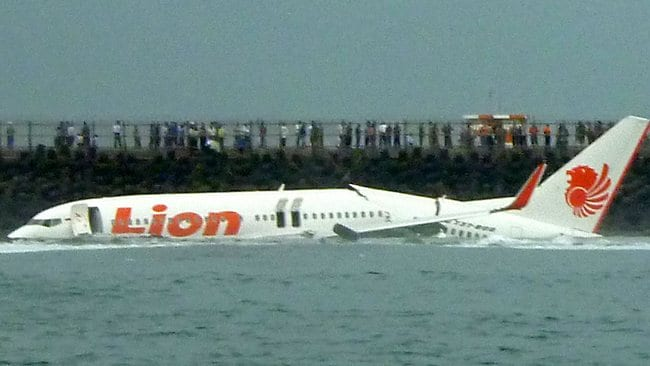 A Lion Air Boeing 737 lies submerged in the water after skidding off the runaway during landing at Bali's international airport near Denpasar.