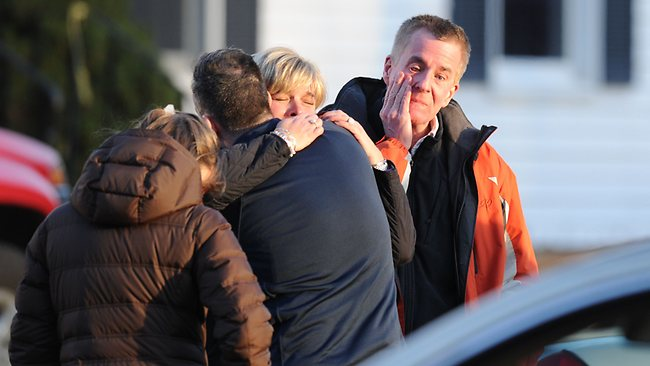 Grieving residents at the scene of the shooting. Picture: AFP