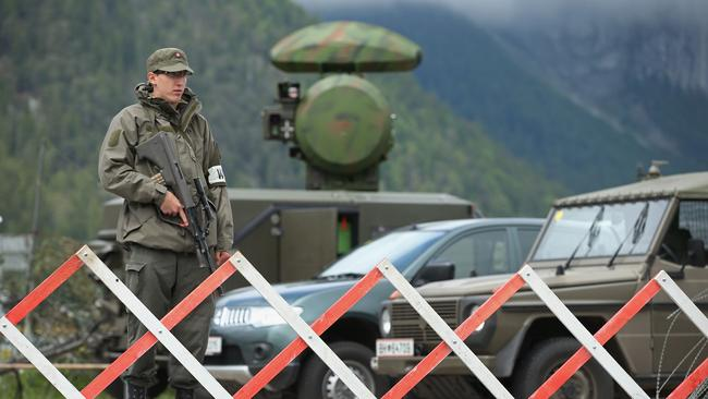 A soldier of the Austrian army stands next to a mobile radar station.