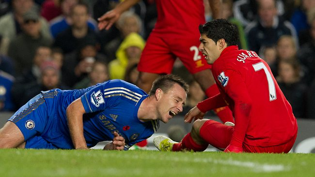 Chelsea's John Terry, left, lies on the pitch after a tackle from Liverpool's Luis Suarez at Stamford Bridge. Terry was carried from the pitch on a stretcher. Picture: Tom Hevezi