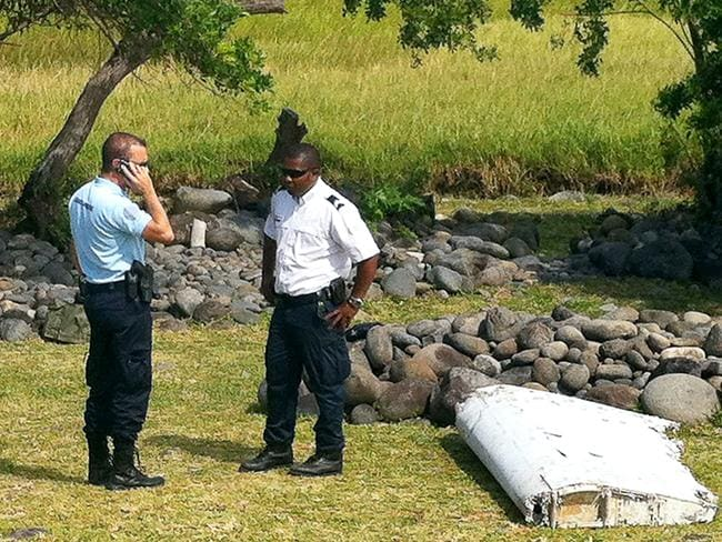 A policeman and a gendarme standing next to a piece of debris later identified from missing Malaysia Airlines plane MH370, found on the French Indian Ocean island of La Reunion. Picture: AFP