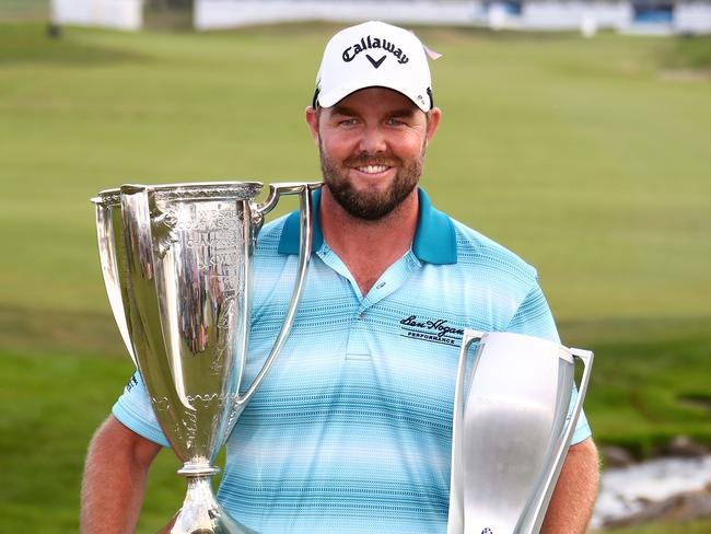 Marc Leishman of Australia poses with the Wadley Cup and the BMW Championship Trophy.