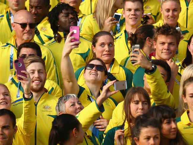 Members of our Commonwealth Games team take selfies as they wait for the Australian team photo.