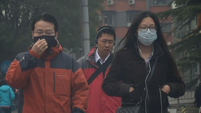 Urgh ... ack ... cough ... Pedestrians wear face masks to protect their lungs from the heavy smog in Beijing. Picture: AP