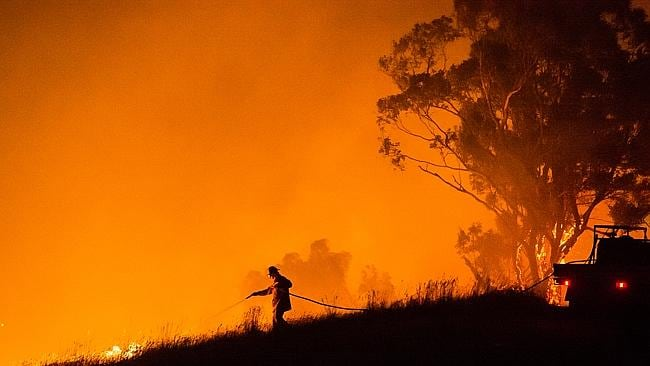 A firefighter tackles a spot fire with a small ute tanker at Morwell on Sunday night.