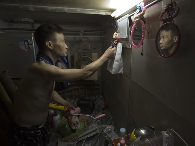 Sin, 55, tidies up the bed in his home. Picture: Kin Cheung/AP
