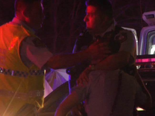 A distressed officer is comforted by colleague at the scene. Picture: TNV