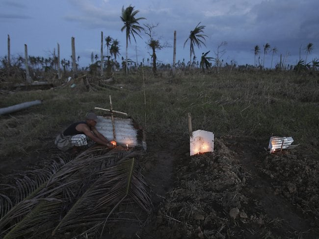 A survivor lights candles on a makeshift grave site of his father and uncle, left, on a field in Palo town, Leyte province, central Philippines. (AP / Aaron Favila, File)