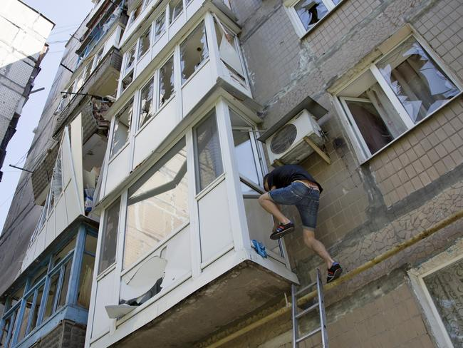Destruction in Donetsk ... a man climbs into his flat in a damaged residential apartment building after the shelling in Donetsk. Picture: Dmitry Lovetsky