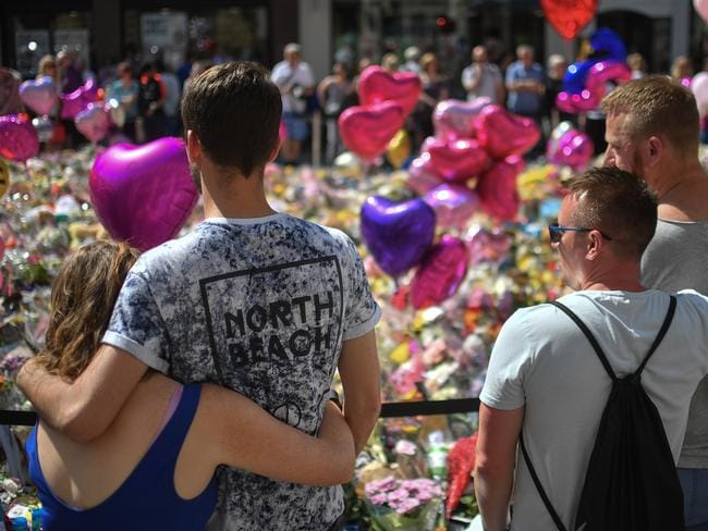 Couples comfort one another as flowers and balloons are left in Saint Ann's Square in tribute to those killed in an explosion at the Manchester Arena. Picture: Getty