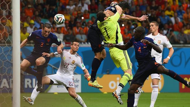 Stefan de Vrij of the Netherlands deflects the ball in for the team's third goal as Iker Casillas of Spain and Robin van Persie of the Netherlands collide in the air.