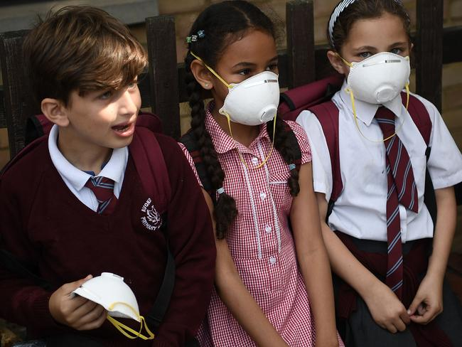 Young children wear masks to protect themselves from clouds of ash and soot that fell on Wednesday. Picture: Carl Court/Getty Images