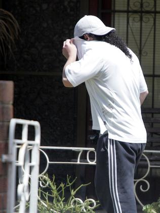 Sharrouf (left) covers his face at his home in Punchbowl, Sydney, in 2011. Picture: Jess Husband.