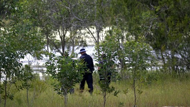 Police scouring the banks of a dam in Kingston. Picture: Jack Tran