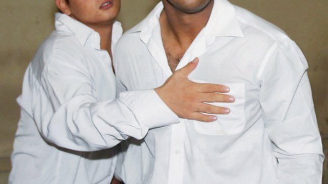 Andrew Chan holds Myuran Sukumaran in a holding cell before their sentencing trials in 2006. Image: Getty.