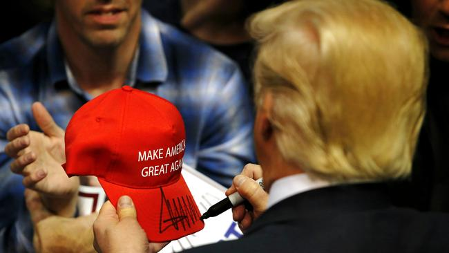 Donald Trump signs a hat for a supporter after speaking at a campaign rally on April 11, 2016 in Albany, New York. Picture: Eduardo Munoz Alvarez/Getty Images/AFP