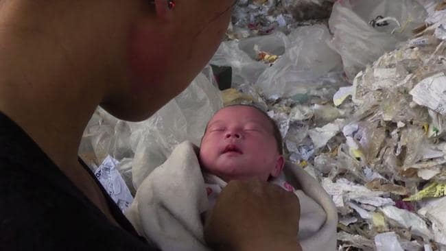 A mother tends to her newborn surrounded by the West's plastic recycling rubbish in the <i>Plastic China </i>documentary.