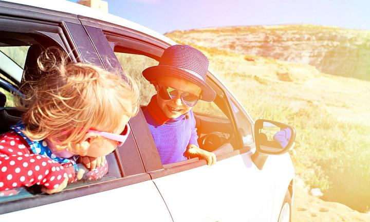 cute little boy and girl travel by car in mountains, family travel