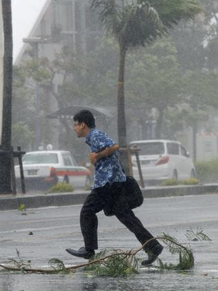 Branches down ... a man walks across a street amid strong winds in Okinawa. Picture: Kyodo News