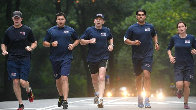 Home run... Mr Abbott jogging with members of the NY fire department. Picture: Jake Nowakowski