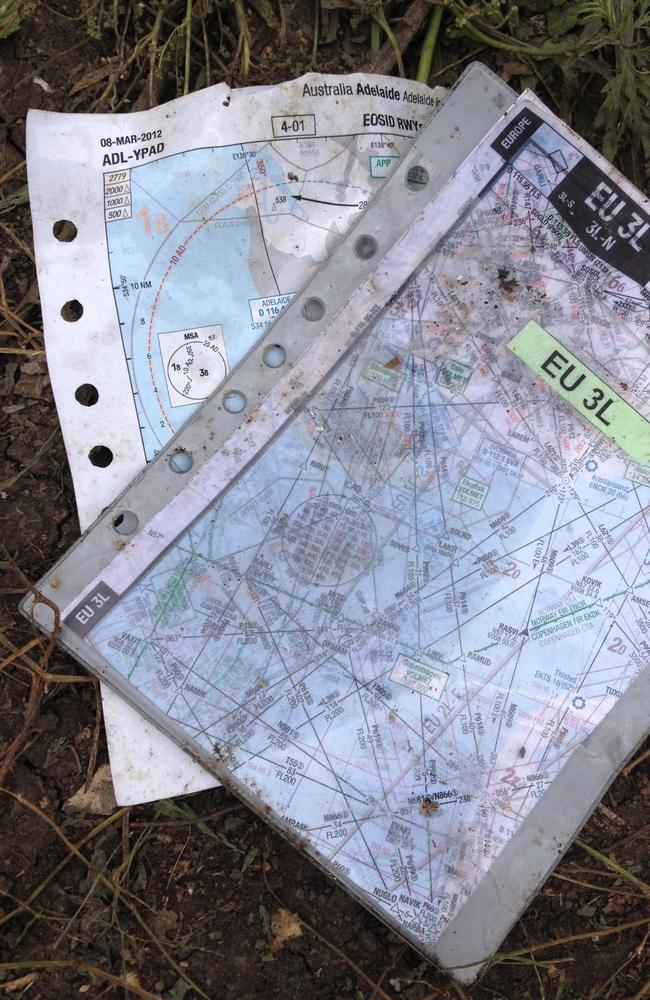 Final flight ... Charts including one denoting Adelaide Airport found scattered in a field about the wreckage of Flight MH17. Picture: Charles Miranda