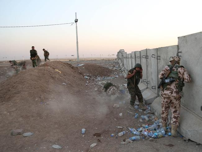 Ducking ... Kurdish Peshmerga fighters take cover during air strikes targeting Islamic State militants near the Khazer checkpoint outside of the city of Irbil in northern Iraq. Picture: AP