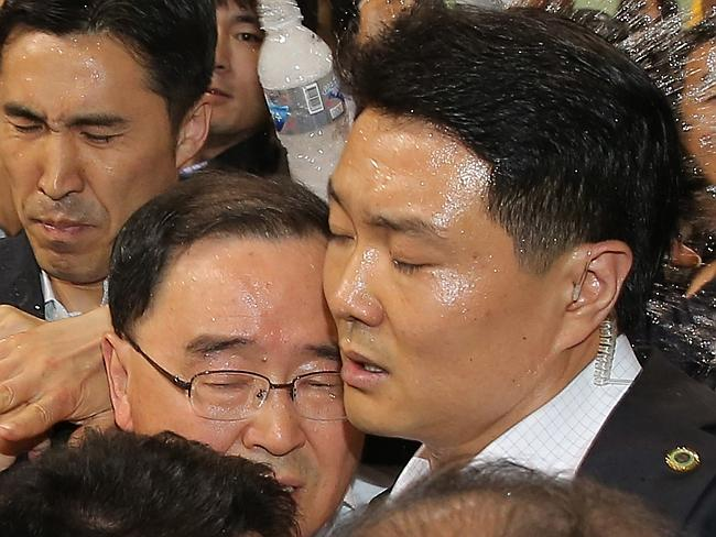 Angry outburst ... South Korean Prime Minister Chung Hong-won is shielded by his bodyguards from a bottle of water thrown by an angry relative of passengers on the Sewol ferry. Picture: Yonhap