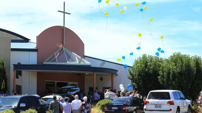 Blue, white and yellow balloons released after the service. Picture: Dean Martin.