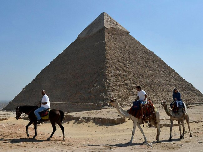Tourists ride camels past the pyramid of Khafre in Giza, southwest of central Cairo. Picture: AFP