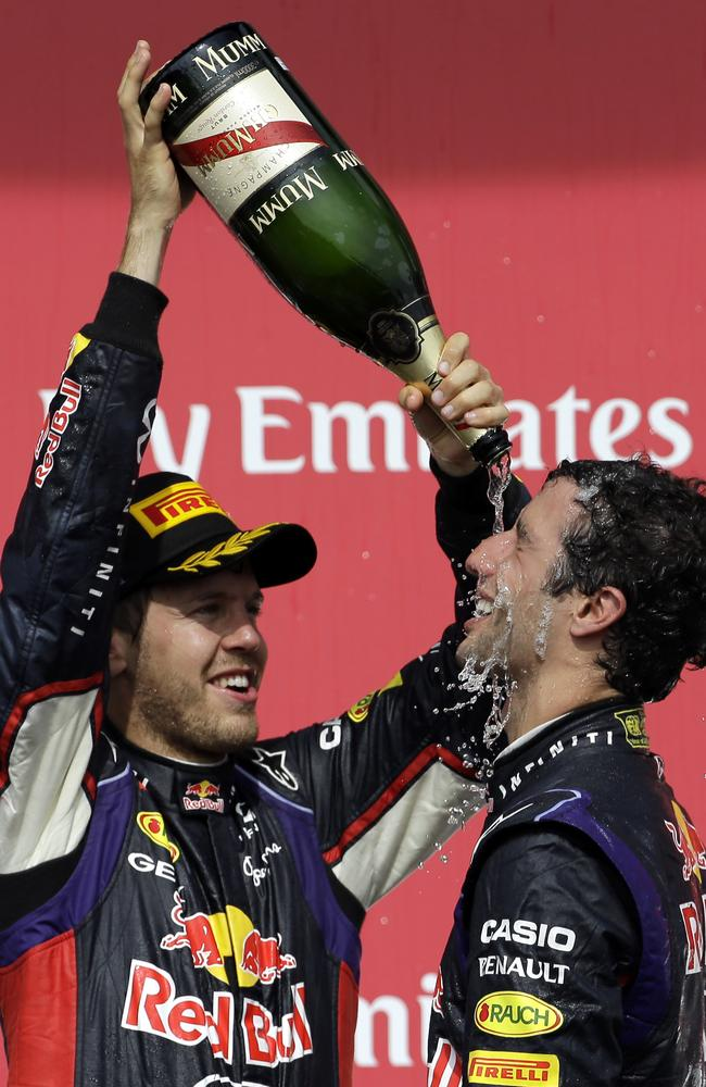 Red Bull driver Sebastian Vettel, left, from Germany, pours champaign over teammate Daniel Ricciardo.