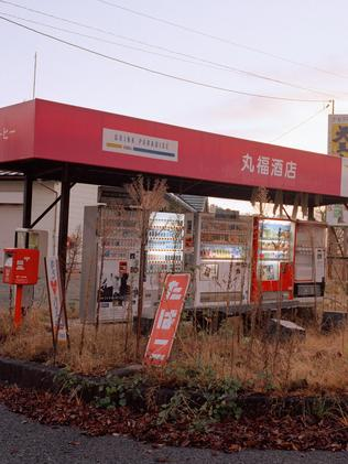 Weeds creep unchecked towards vending machines at an abandoned filling station in Tsushima pictured in Shadowlands series by Robert Knoth.