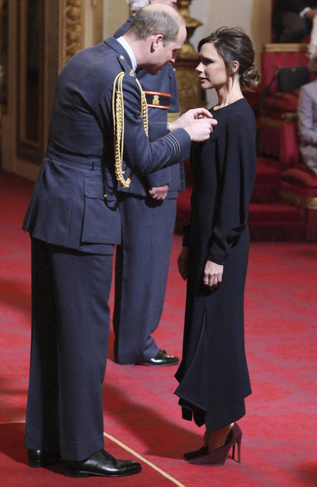 Fashion designer Victoria Beckham, right, receives her OBE from Britain's Prince William, the Duke of Cambridge during an investiture ceremony at Buckingham Palace in London. Picture: Yui Mok/PA via AP