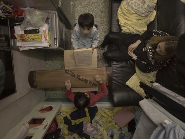 Li Suet-wen is pictured with her two children in their cramped home. Picture: Kin Cheung/AP