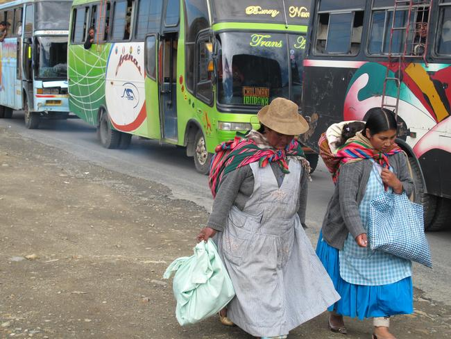 Local women walking past some of the less-luxury buses outside La Paz. Picture: Kimberly Gillan.